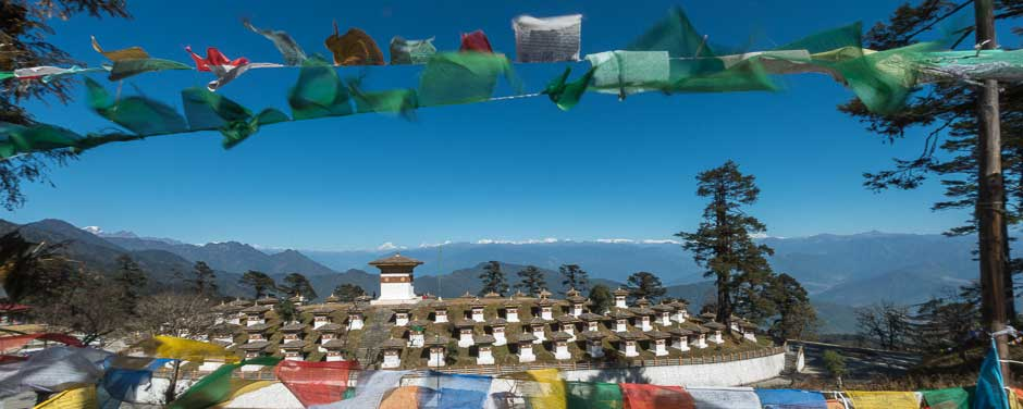 Bhutan, Dochu La pass, and Buddhist prayer flags and 108 stupas, and the white peaks of the Himalayas are in the background.