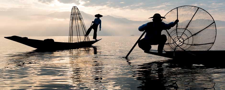A silhouette of leg-rowing fishermen on Inle Lake, Myanmar