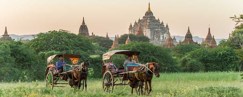 Pony carts with temples in the background at sunset Bagan, Myanmar