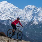 Annie mountain biking Mustang Nepal, in the Annapurna region, behind are Nigiri Peak and Annapurna south
